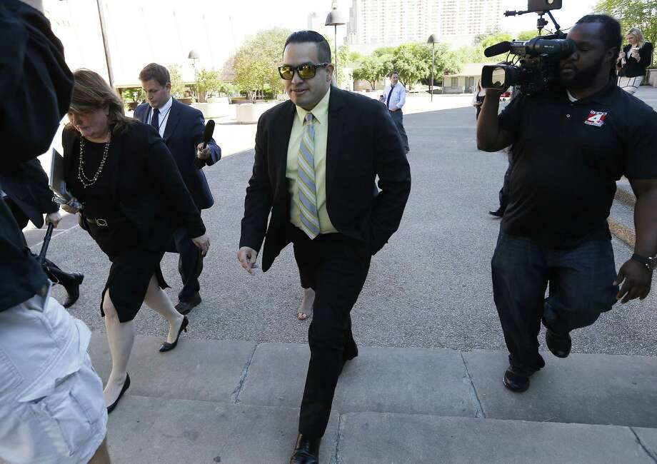 San Antonio Police Officer Robert Encina leaves the John Wood Federal Courthouse on Thursday, Apr. 6, 2017 after a federal jury found Encina and the city were not liable for the February 2014 shooting of Marquise Jones. Walking beside Encina was City Assistant Attorney Debbie Klein. (Kin Man Hui/San Antonio Express-News) Photo: Kin Man Hui /San Antonio Express-News / ©2017 San Antonio Express-News