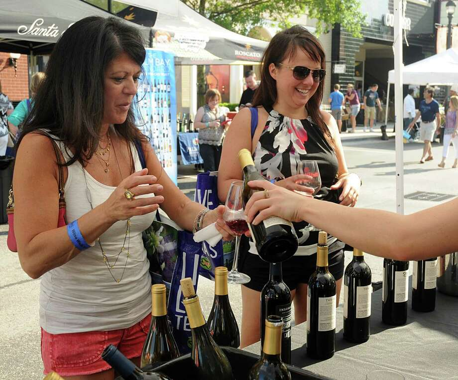 Christine Rubeis and Nancy Chafe, both of The Woodlands, sample wine at a booth during the H-E-B Wine Walk at Market Street in 2015. This year's event is June 5-11 in The Woodlands. Photo: David Hopper, Freelance / freelance
