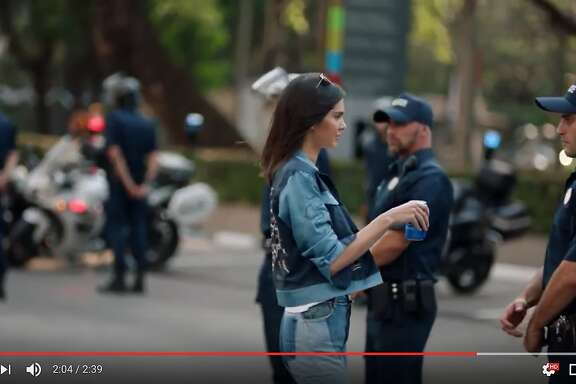 This is a screenshot of a Pepsi Co. advertisement showing Kendall Jenner approaching a police officer with a can of Pepsi Cola.