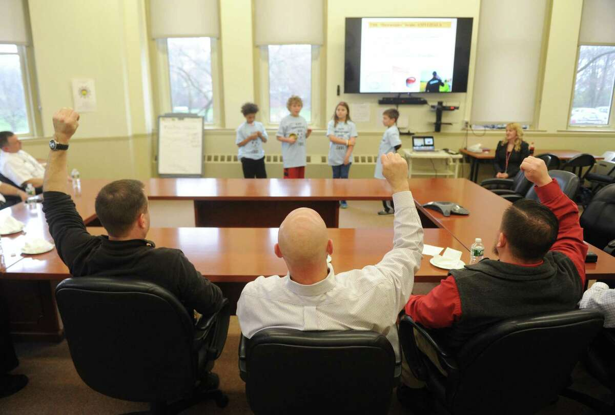 Sgt. Brent Reeves, left, Special Victims Section Detective Charles Eible, center, and Special Victims Section Detective John King raise their arms for an exercise during a mindfulness presentation to Greenwich first responders at the Board of Education in Greenwich, Conn. Thursday, April 6, 2017. Representatives from the Greenwich police, fire and EMS services learned about mindfulness and stress-management strategies that can be helpful in their day-to-day work.
