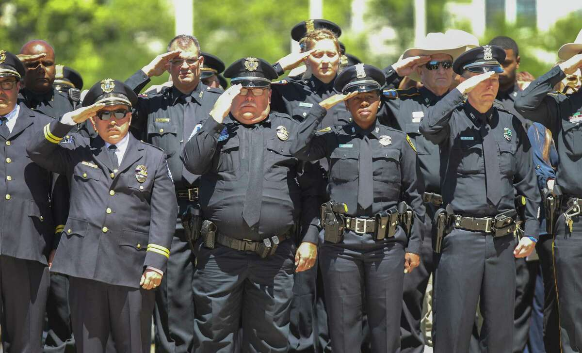 Law enforcement officers stand at attention as the casket of Harris County Pct. 3 Assistant Chief Deputy Constable Clinton Greenwood leaves the Second Baptist Church on 6400 Woodway Thursday, April 6, 2017, in Houston.