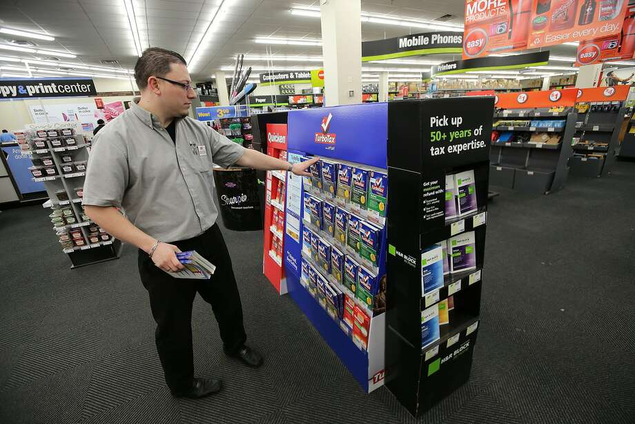 Manager Cesar Solares arranges the TurboTax and H&R Block tax software display at the Staples in Somerville, Mass. Photo: Boston Globe, Boston Globe Via Getty Images