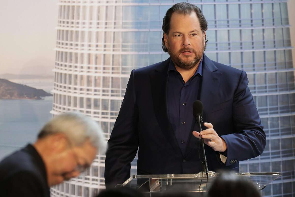 Marc Benioff, CEO of Salesforce speaks to the gathering after being introduced by Mayor Ed Lee, (left) during a topping off ceremony as the final steel beam is being set to be moved into position on the Salesforce Tower in downtown San Francisco, Ca. on Thurs. April 6 2017.