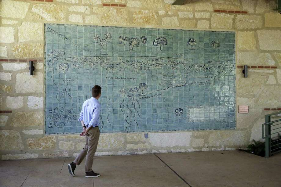 """Communications Administrator Konnor Frazier views the Bodine Gate tile mural, """"Acequia Madre Map"""" inside the grounds at the Witte Museum on April 4. It shows the historic acequias from early San Antonio. Photo: Tom Reel /San Antonio Express-News / 2017 SAN ANTONIO EXPRESS-NEWS"""