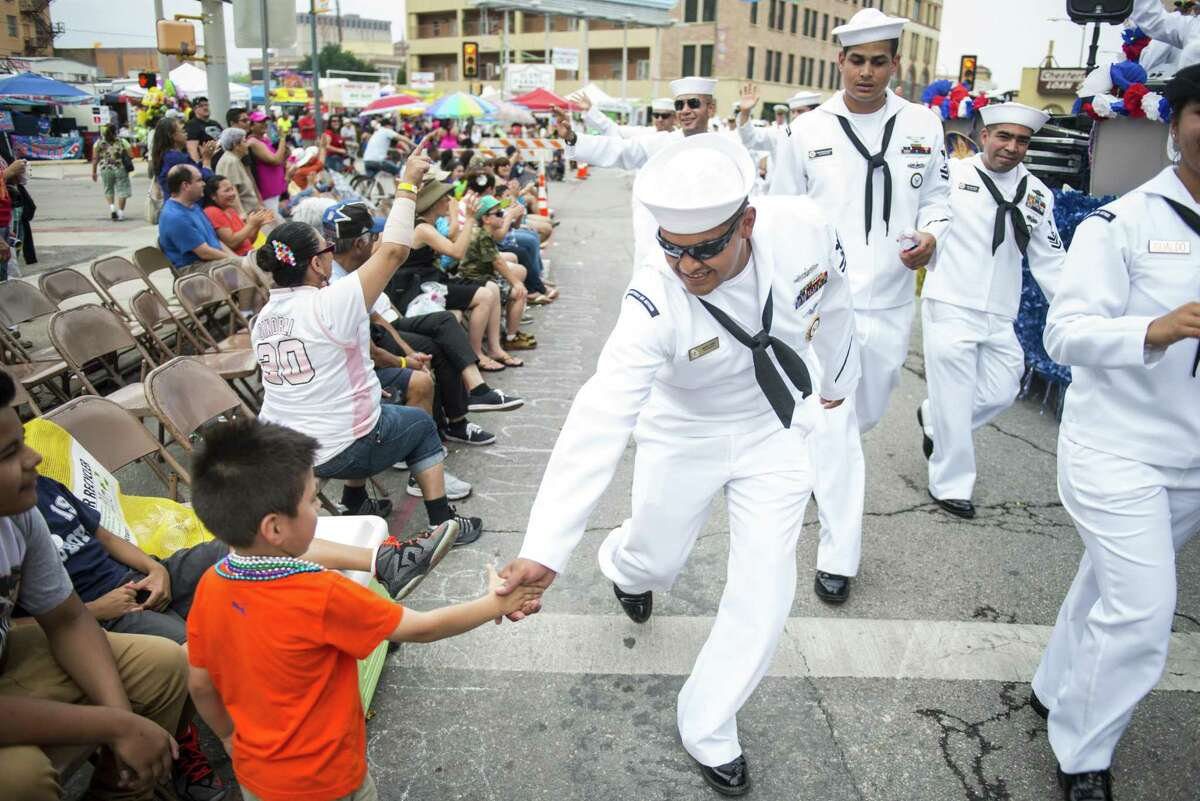 Marcelo Luna, 4, gets a handshake from passing military members during San Antonio Fiesta's Battle of Flowers parade April 24, 2015, through downtown San Antonio.