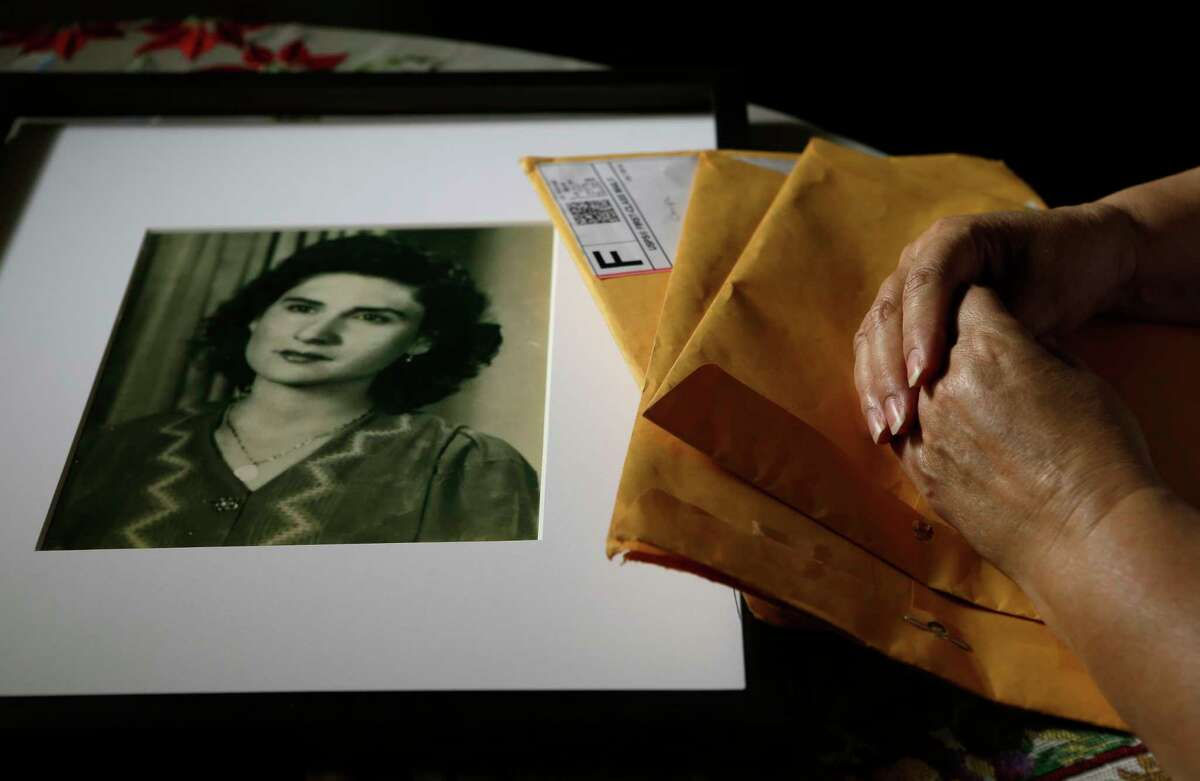 Cris Chapa, overlooking a 1945 photo of her mother, Manuela, while holding three envelopes that delivered the news of what happened to her two years ago at Kindred Hospital Sugar Land.