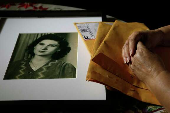 The hands of Cris Chapa are shown along with a 1945 photo of her mother, Manvela Chapa, at age 18, and the anonymous letters the family received nearly two years after her death in 2015 taken Wednesday, April 5, 2017. The information revealed their 87-year-old mother hadn't died of natural causes, as they'd been led to believe, but rather after a doctor performed an operation without their consent. They later learned the information came from one of the nurses at the Sugar Land hospital where their mother died.