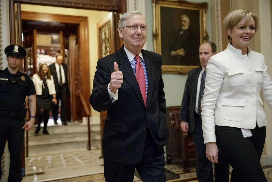 Senate Majority Leader Mitch McConnell of Kentucky signals that Neil Gorsuch's confirmation to the U.S. Supreme Court is on track as he leaves the Senate chamber on Capitol Hill. Gorsuch is expected to be confirmed on a simple-majority vote. Photo: J. Scott Applewhite, Associated Press