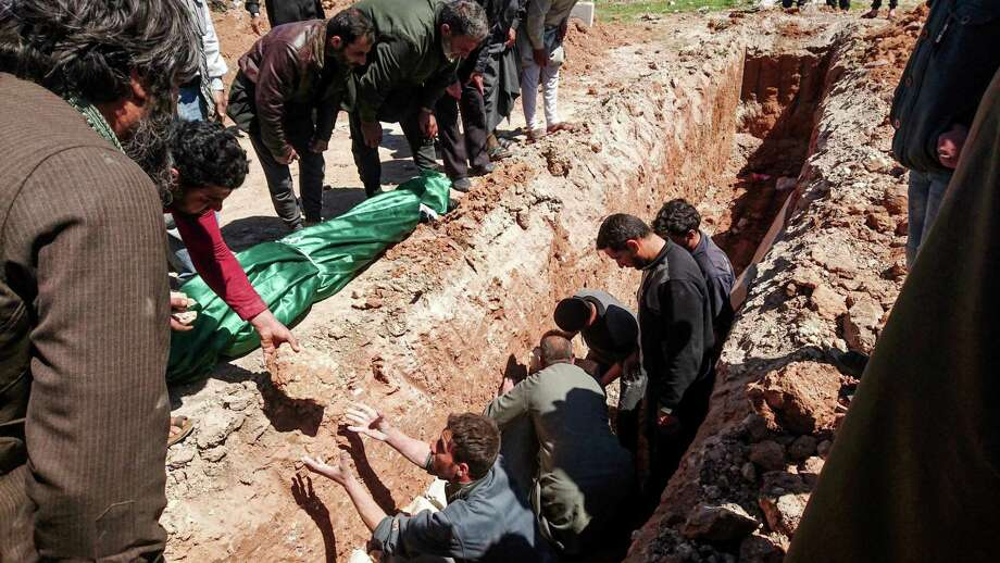 Syrians bury the bodies of victims of a a suspected toxic gas attack in Khan Sheikhun on Wednesday. President Trump is correct in citing Obama administration inaction as a cause, but the fact is, he's president, and the problem is now his. Photo: FADI AL-HALABI /AFP /Getty Images / AFP or licensors