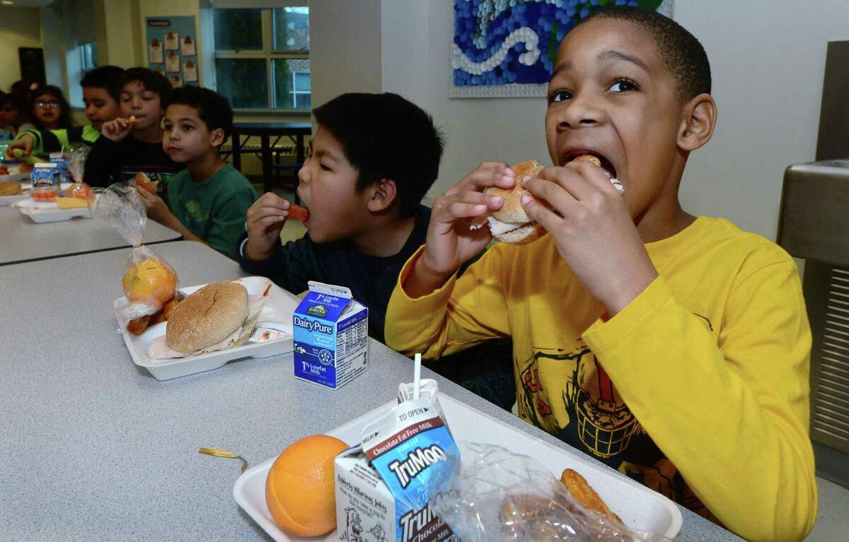 Brookside Elementary School second-grader Derek Oliver, right, eat lunch on Thursday at the school in Norwalk. A report on Norwalk Public Schools food service operations found a need for widespread change, citing issues such as poor food quality, lackluster leadership, minimal scratch-made food and more.