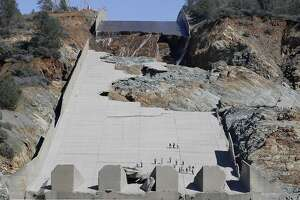 "FILE-  In this Feb. 28, 2017 file photo, officials inspect Oroville Dam's crippled spillway in Oroville, Calif. A team of experts is warning of a ""very significant risk"" if the main spillway of the California dam is not operational again by the next rainy season. The warning is contained in a report obtained Wednesday, March 22 by The Associated Press. (AP Photo/Rich Pedroncelli)"