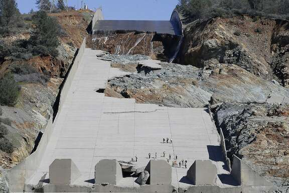 """FILE-  In this Feb. 28, 2017 file photo, officials inspect Oroville Dam's crippled spillway in Oroville, Calif. A team of experts is warning of a """"very significant risk"""" if the main spillway of the California dam is not operational again by the next rainy season. The warning is contained in a report obtained Wednesday, March 22 by The Associated Press. (AP Photo/Rich Pedroncelli)"""