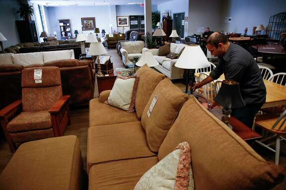 Houston Furniture Bank assistant sales manager Pedro Cisneros moves lamps Thursday in the outlet center at the furniture bank's new 75,000-square-foot facility off Mosley Road on the day of the new warehouse's ribbon cutting.