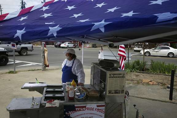 Mike Williams, (right) of Cameron Park sets up his hot dog stand at George's auto repair shop in El Dorado, Ca. on Wed. April 5 2017, where he raises funds that help local veterans in need.