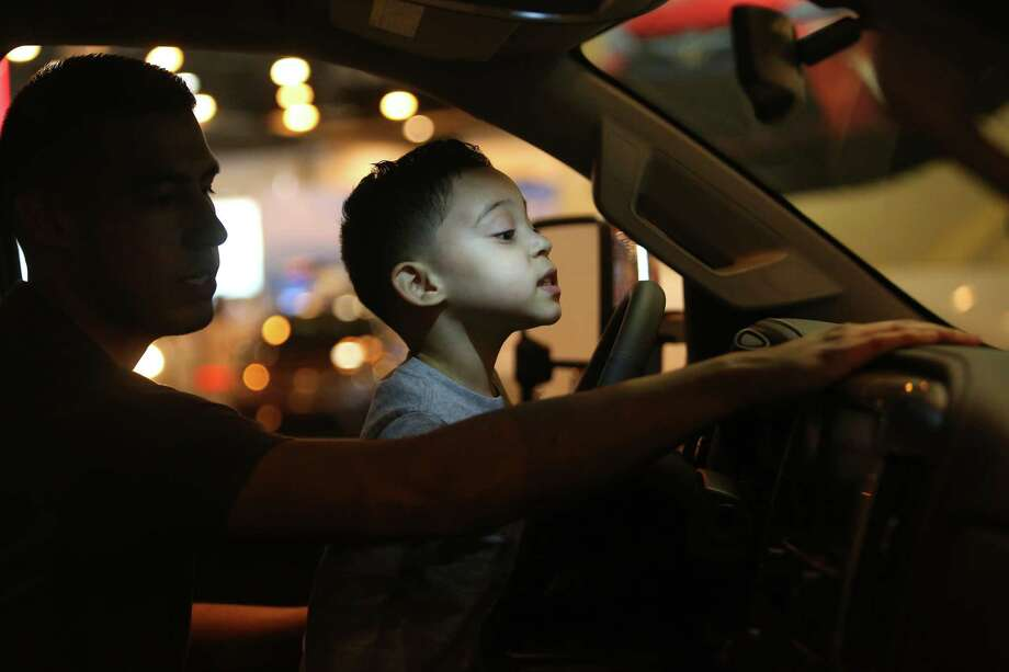 Ian Castaneda, 3, sits on the lap of his father, Aaron, as they check out a truck Thursday at the Houston Auto Show.  Photo: Mark Mulligan, Staff Photographer / 2017 Mark Mulligan / Houston Chronicle