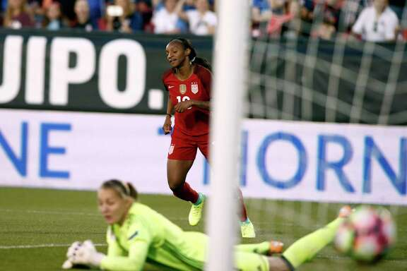 Crystal Dunn of the United States scores one of her two goals against Russian goaltender Alena Belyaeva in the first half of Thursday's match at Frisco.