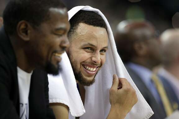Stephen Curry (30) smiles on the bench with Kevin Durant (35) as the Golden State Warriors played the Minnesota Timberwolves at Oracle Arena in Oakland, Calif., on Tuesday, April 4, 2017.