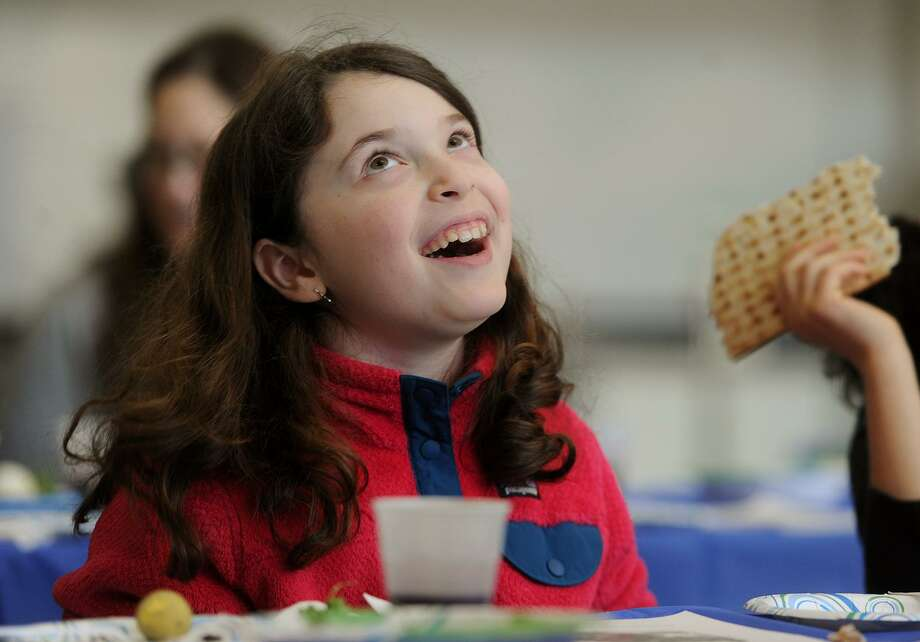Julia Zagar, 9, of Fairfield, Conn. sings along to a song about matzah during a Passover Seder. Photo: Brian A. Pounds / Hearst Connecticut Media / Connecticut Post