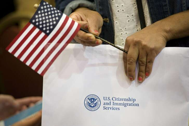 "A woman holds a miniature American flag and her papers during a naturalization ceremony in San Diego, California, U.S., on Wednesday, March 22, 2017. Hawaii's attorney general is seeking to extend a temporary restraining order blocking Donald Trump's revised travel ban, citing the president's own words as evidence that the new policy is merely a ""subterfuge."" Photographer: David Maung/Bloomberg"
