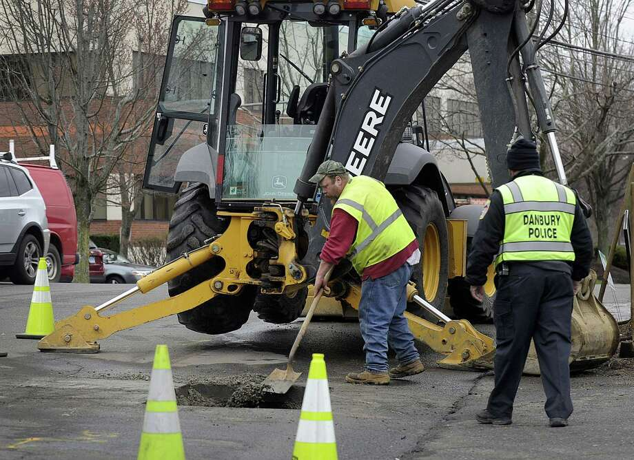 Aaron Price with the Danbury Water Department, center, is part of a crew repairing a broken water main at the intersection of Great Plain and Germantown Roads in front of Jimmies's Market, Friday morning, April 7, 2017. Photo: Carol Kaliff / Hearst Connecticut Media / The News-Times