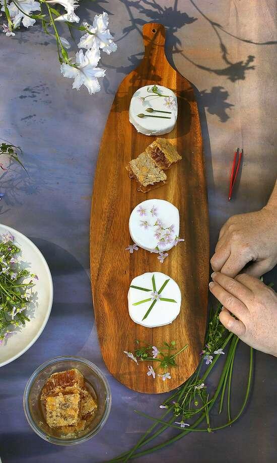 Stefani Bittner decorates cheese rounds with edible flowers. Photo: Liz Hafalia, The Chronicle