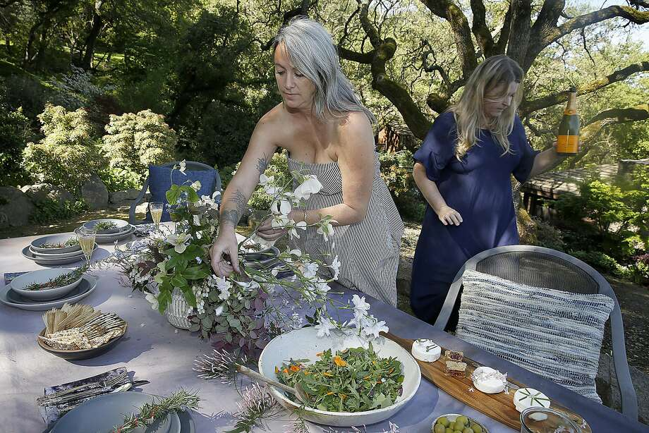 Floral designer Alethea Harampolis (middle) works on arrangement for the spring/summer table setting as author Stephanie Bittner (right) sets the table on Tuesday, April 4, 2017, in Lafayette, Calif. Photo: Liz Hafalia, The Chronicle