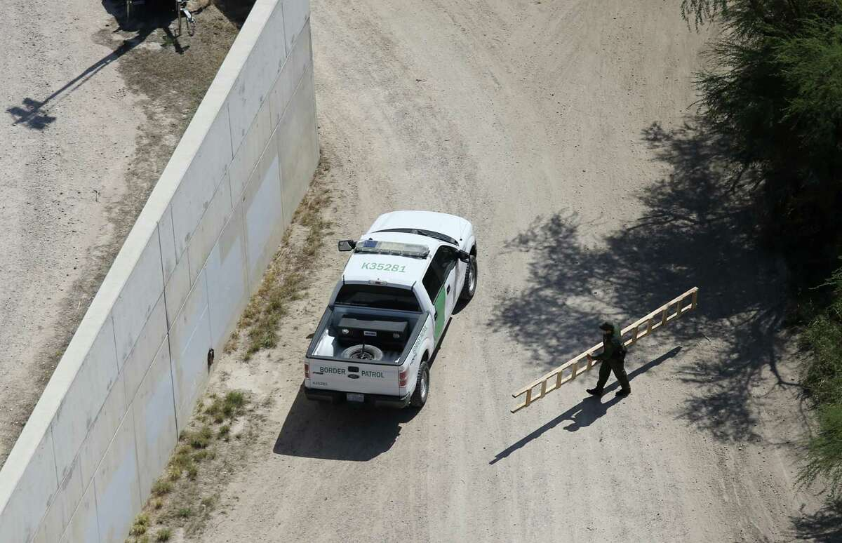 A U.S. Border Patrol agent picks up a ladder hidden in the field by the U.S. Mexico border wall, left, near the McAllen-Hidalgo International Bridge, Tuesday, Oct. 4, 2016. A unit with the U.S. Customs and Border Protection Air and Marine Operations flying a Bell Huey helicopter spotted the ladder. Smugglers use ladders to crossing immigrants and drugs over the wall.