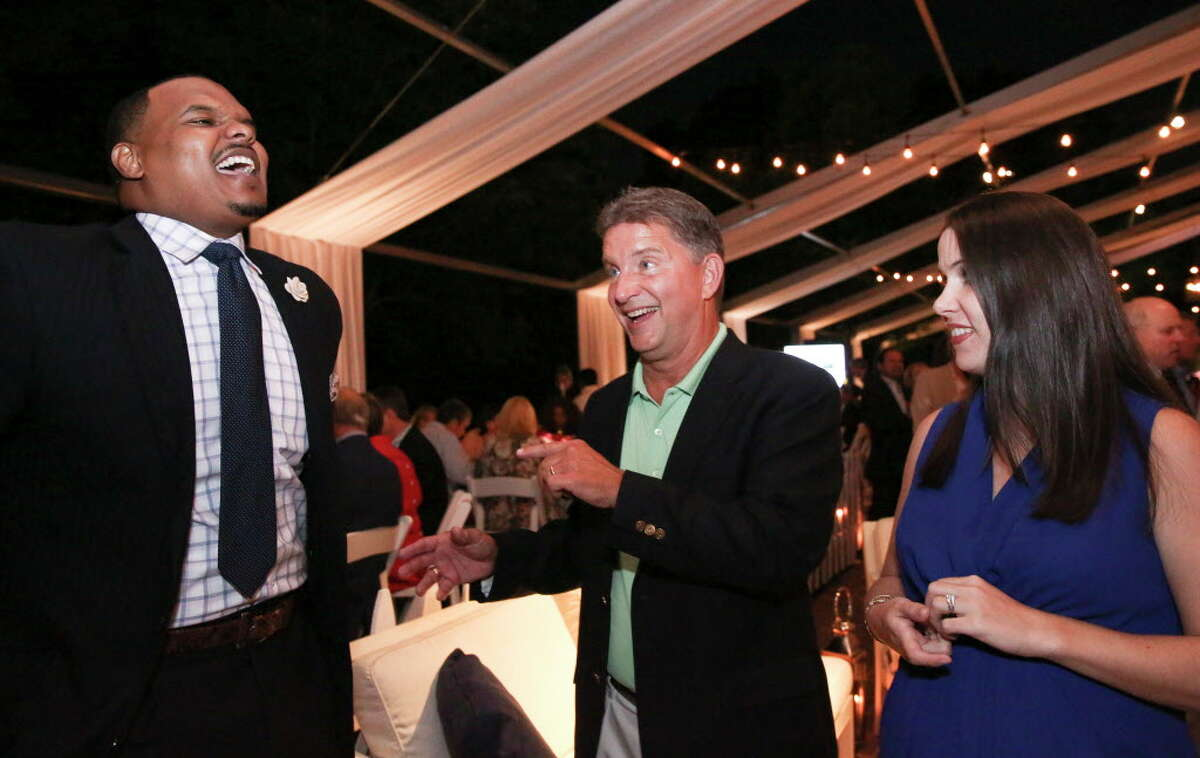 Chester Pitts, left, emcee of the night, laughs out loud during a conversation with Gene Fisseler and his daughter Allison Thompson at Trees For Houston's 23rd Annual Root Ball at the Bayou Club Thursday, April 6, 2017, in Houston.