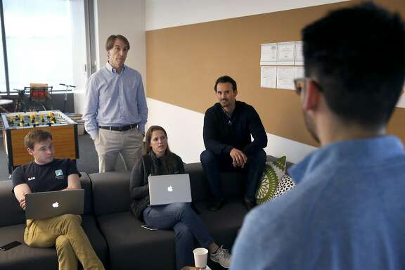 Wealthfront co-founders, CEO Andy Kachleff (standing) and Chief Strategy Officer Dan Carroll (center), attend a meeting with colleagues in the company's offices in Redwood City, Calif. on Thursday, April 6, 2017.