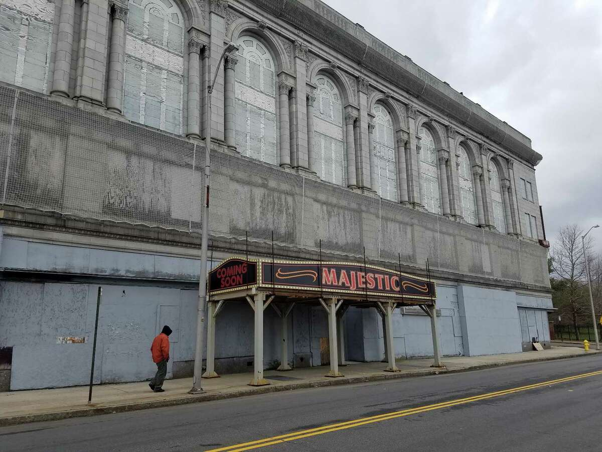 A man walks toward the faux marquee the city has placedin front of thePoliPalaceandMajesticTheaterin anticipation of the announcement of the bidder chosen to revive the complex.