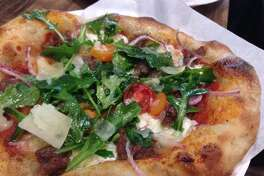 The Italiano pizza (red sauce, mozzarella, red onion, Italian sausage, mizuna and arugula) from Arte Pizzeria, a new concept opening in the Conservatory food hall in downtown Houston.