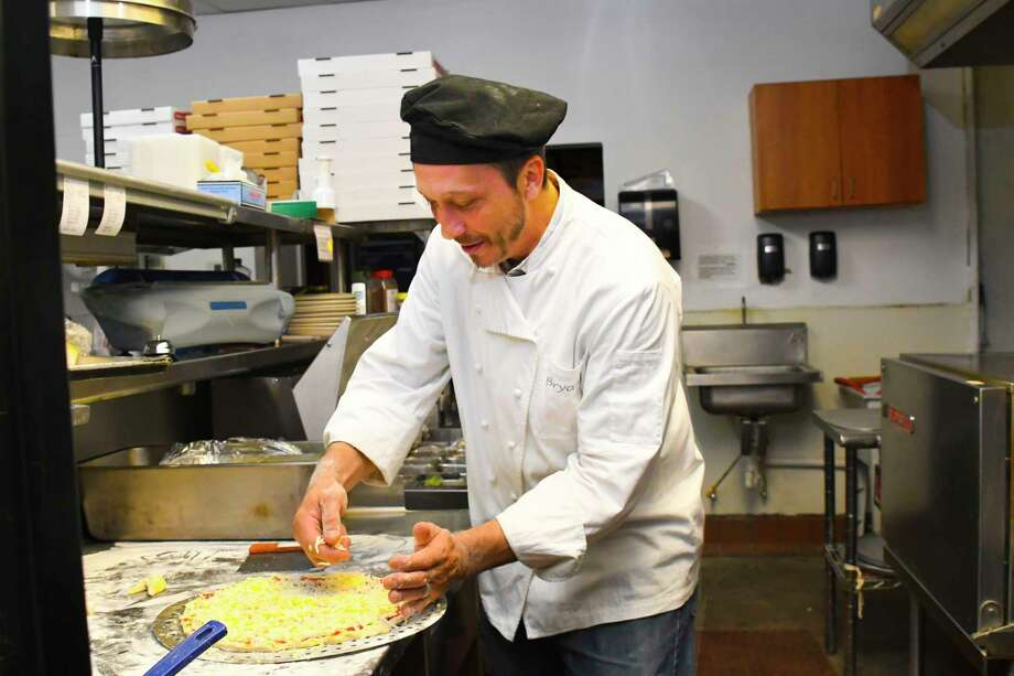 Chef Bryan Engledow prepares the sauce and cheese on the pizza.. Photo: Tony Gaines, Photographer