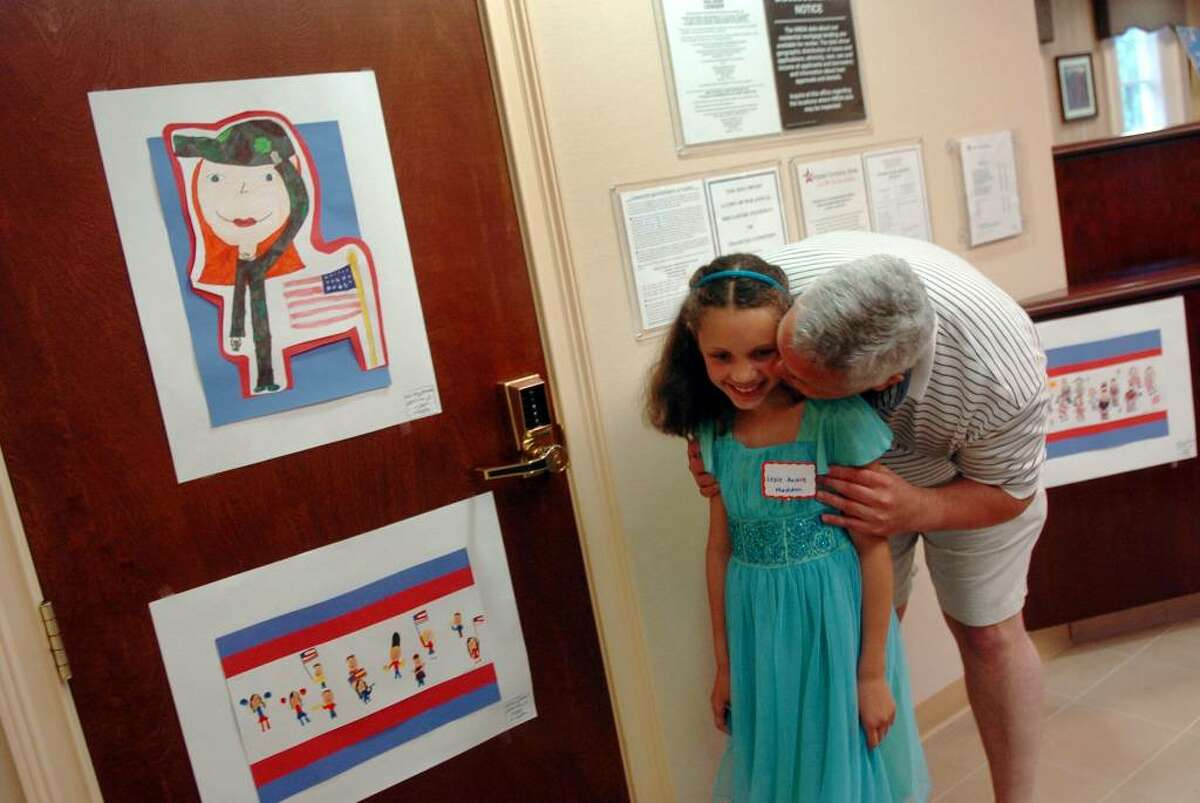 """Lexi Anne Madden, a second grader from McKinley School, gets a kiss from her father Glenn at the Patriot National Bank along Black Rock Turnpike in Fairfield, Conn. on Tuesday June 1, 2010. Madden, whose piece is at the top left in photo, won first place in the """"What Does Memorial Day Mean to Me?"""" contest held by the school and on display at the bank."""