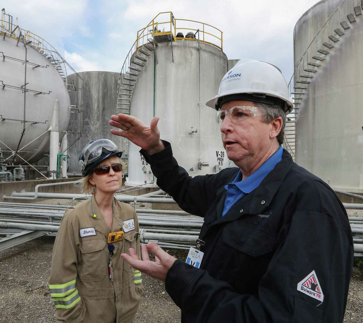 Emerson executive account manager Randy Mobley, with OXEA Corp. senior instrument/electrical engineer Sherri Law, explains the workings of wireless transmitters on a storage tank in Bay City.