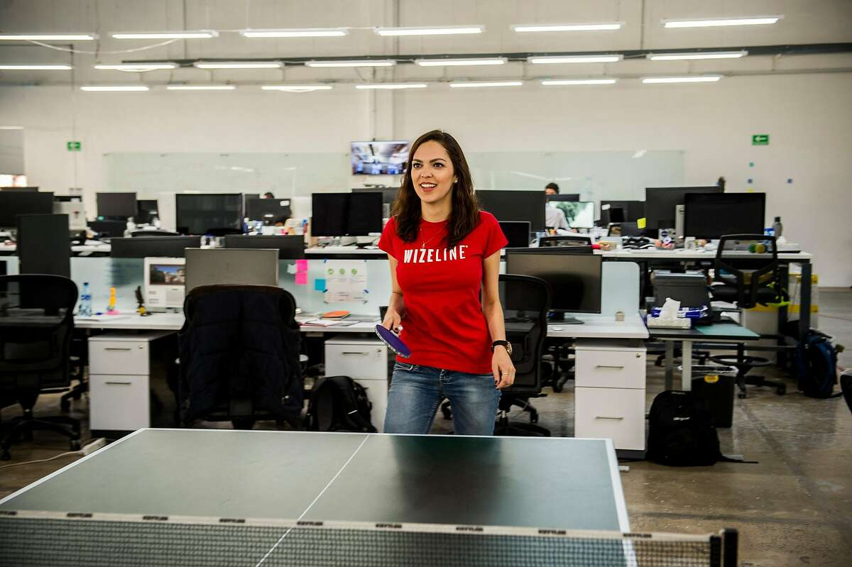 """Jazmin Ruiz employee of Wizeline work on laptop computers at the Wizeline Inc. office in Guadalajara, Mexico, on Friday, April 07, 2017. Wizeline, a San Francisco startup that does """"intelligent software,"""" has opened up a Guadalajara office, in Mexico's tech hub. A reason behind them opening it is because the visa rules there are easier, compared to the U.S"""