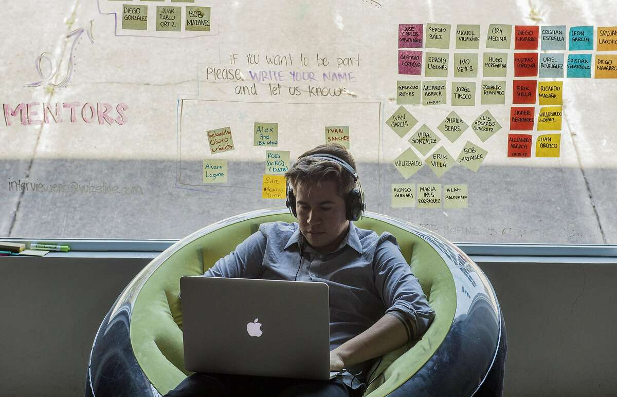 """Diego Aguado employee of Wizeline work on laptop computers at the Wizeline Inc. office in Guadalajara, Mexico, on Friday, April 07, 2017. Wizeline, a San Francisco startup that does """"intelligent software,"""" has opened up a Guadalajara office, in Mexico's tech hub. A reason behind them opening it is because the visa rules there are easier, compared to the U.S"""
