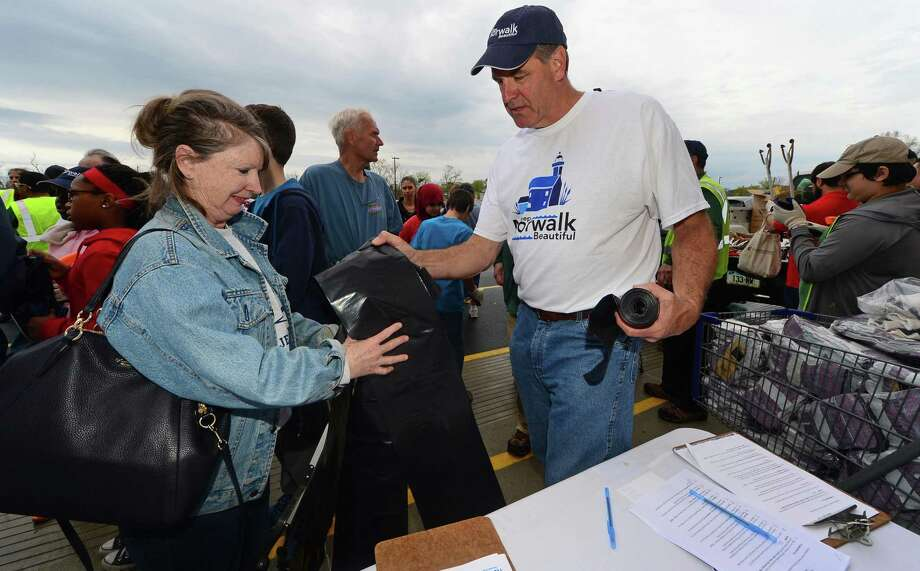 Volunteer Ellen Sentz gets garbage bags from City of Norwalk Neighborhood Improvement Coordinator, David Shockley, as they join Norwalk Mayor Harry and his wife Lucia Rilling at Lowe's in Norwalk, Conn. to kick off Norwalk's Citywide Spring Clean-Up on Saturday, April 23, 2016. Photo: Erik Trautmann / Hearst Connecticut Media / (C)2016, The Connecicut Post, all rights reserved