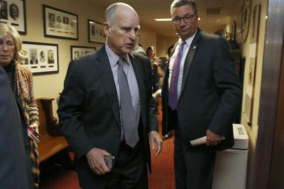 Gov. Jerry Brown walks into a meeting of the Senate Democratic Caucus to urge them to approve a transportation plan,Thursday, April 6, 2017, in Sacramento, Calif. Brown and top legislative leaders pressed all week to convince fellow Democrats to support the measure that would place a $5-billion-a-year boost in California's gas and vehicle taxes to pay for major road repairs. (AP Photo/Rich Pedroncelli)