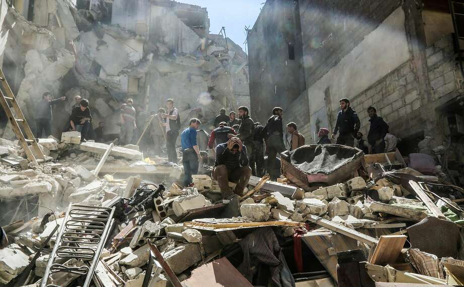 A Syrian mourns as members of the Syrian civil defence volunteers, also known as the White Helmets, and people search for survivors from the rubble following reported air-strikes on the rebel-held town of Saqba, in Eastern Ghouta, on April 4, 2017. Photo: AMER ALMOHIBANY, AFP/Getty Images