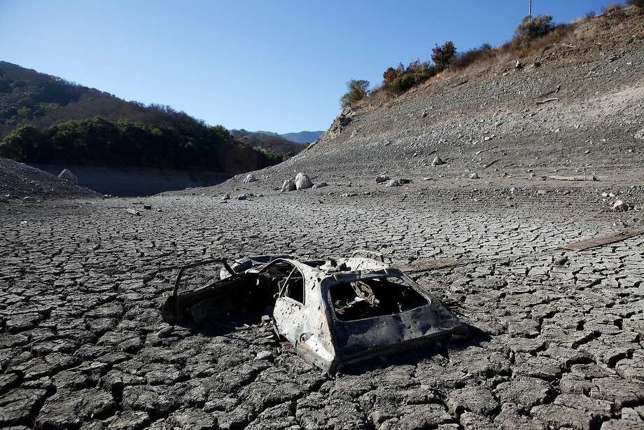 During the state's recent drought, the Almaden Reservoir in San Jose went dry, revealing in 2014 a car that had been dumped in the lake. The federal government's latest National Climate Assessment says California can expect more extreme swings between droughts  and floods  unless greenhouse gas emissions are cut sharply. Photo: Michael Short, The Chronicle