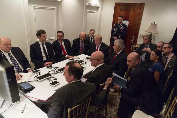 In this image provided by the White House, President Donald Trump receives a briefing on the Syria military strike from his National Security team after the strike at Mar-a-Lago in Palm Beach, Fla., Thursday night, April 6, 2017. Sections Of The Image Were Blurred Or Masked By The Source For Security Reasons. (White House via AP)
