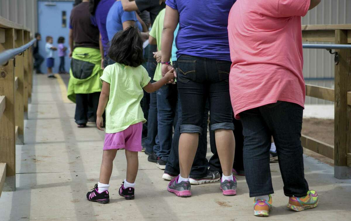 Residents line up to eat lunch at the South Texas Family Residential Center that houses thousands of women and children caught crossing the border illegally, seeking asylum in the U.S., in Dilley, Texas, May 14, 2015.