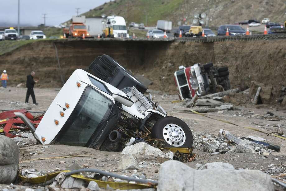 FILE- In this Feb. 18, 2017, file photo, officials look over the scene where a tractor trailer fell from southbound Interstate 15 where part of the freeway collapsed due to heavy rain in the Cajon Pass, Calif. State lawmakers are nearing a vote on a plan to raise taxes and fees for road construction, barely a week after Gov. Jerry Brown and top legislative leaders revealed their negotiated agreement and began rushing it through the Legislature. (David Pardo/The Daily Press via AP, file) Photo: David Pardo, Associated Press