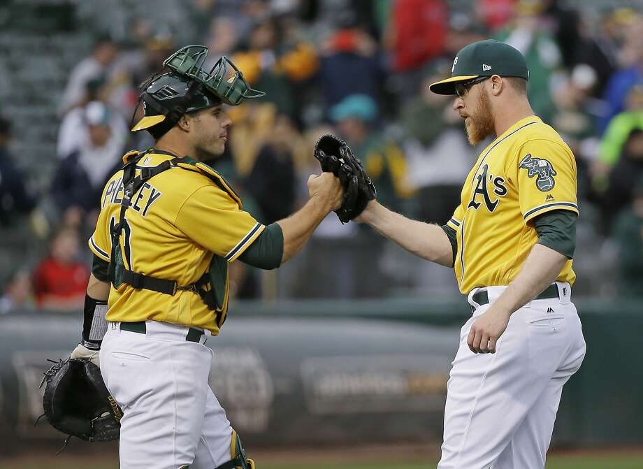 Oakland Athletics relief pitcher Sean Doolittle, right, is greeted by catcher Josh Phegley at the end of the team's baseball game against the Los Angeles Angels on Thursday, April 6, 2017, in Oakland, Calif. Oakland won 5-1. (AP Photo/Eric Risberg) Photo: Eric Risberg, Associated Press