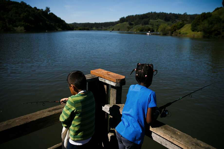 Above: Eight-year-old Marco David (left) and 7-year-old Marietou Keita fish on the docks at Lake Chabot in Castro Valley. Below: Richard Seward and stepdaughter Ceanarionn Smith Woods, 4, afloat on Lake Chabot, look over a bird guide. Photo: Mason Trinca, Special To The Chronicle