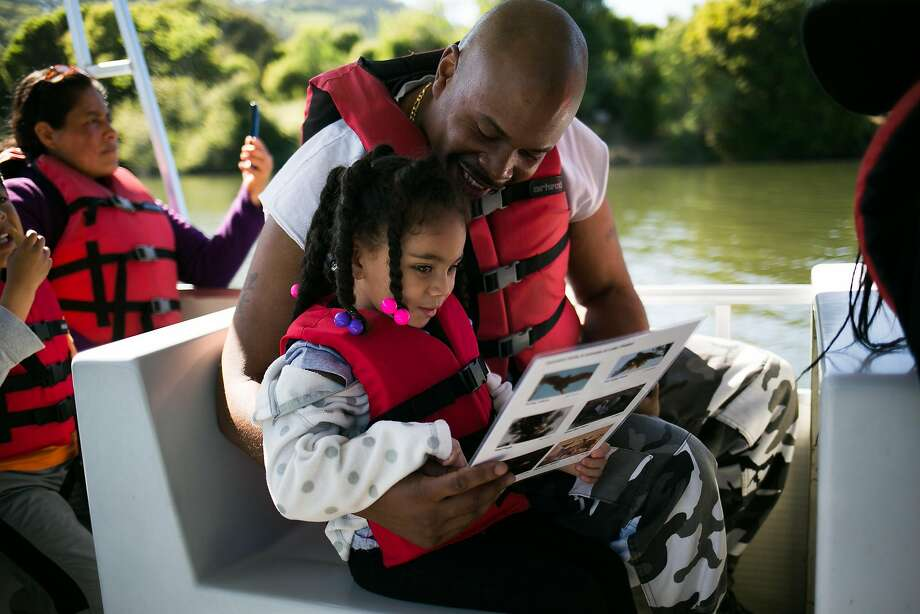 Richard Seward and stepdaughter Ceanarionn Smith Woods, 4, look over a bird identification card as they boat on Lake Chabot in Castro Valley. Photo: Mason Trinca, Special To The Chronicle