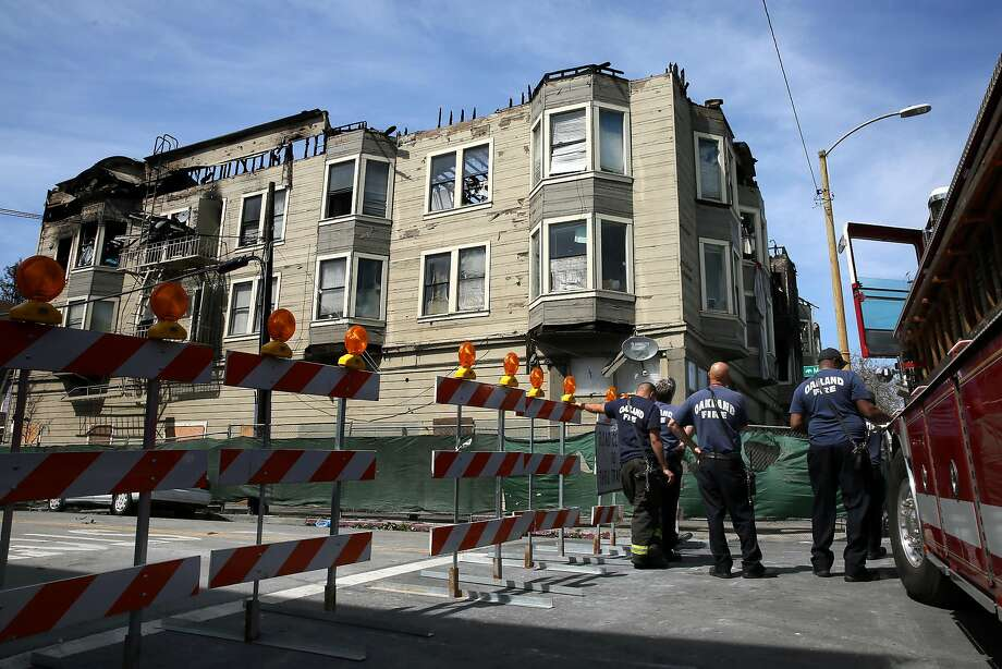 Firefighters inspect damage from a blaze last month at a halfway house in West Oakland. Officials call the city's building database jumbled and incomplete. Photo: Michael Macor, The Chronicle