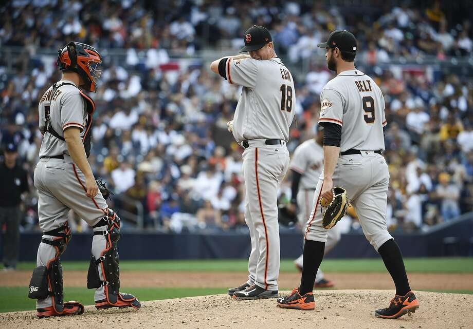 Catcher Nick Hundley and first baseman Brandon Belt approach Matt Cain just before Cain was removed in the fifth inning. Photo: Denis Poroy, Getty Images