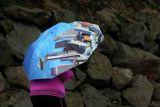 A woman walks through the Wedgewood neighborhood with a Seattle-themed umbrella as high winds and rain storms roll through the Puget Sound region, Friday, April 7, 2017.
