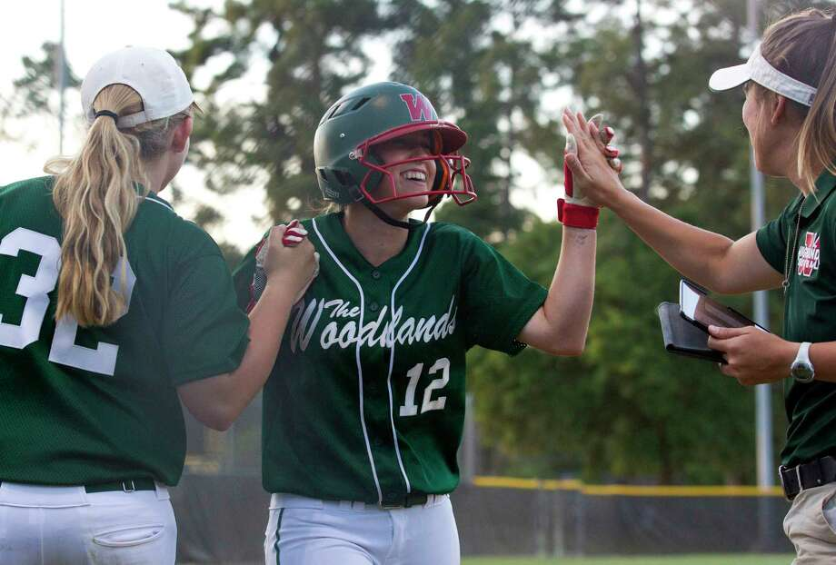 Skylar Stockton #12 of The Woodlands gets a high-five after scoring on of three runs on Amanda Curran's three RBI double during the third inning of a District 12-6A high school softball game Friday, April 7, 2017, in The Woodlands. Photo: Jason Fochtman, Staff Photographer / © 2017 Houston Chronicle